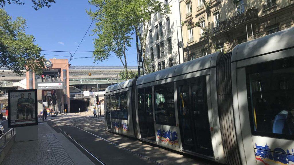 Tram en station à Suchet avec vue sur la gare de Perrache