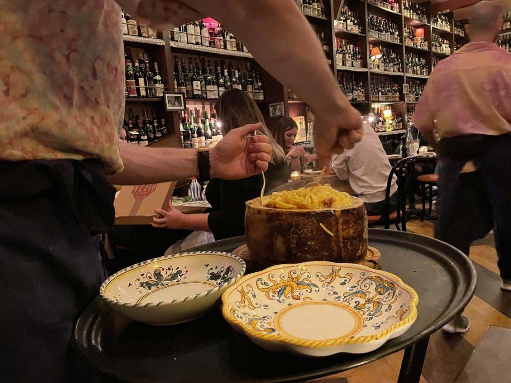 Le serveur plonge les pâtes dans la meule de pecorino chez Carmelo à Lyon